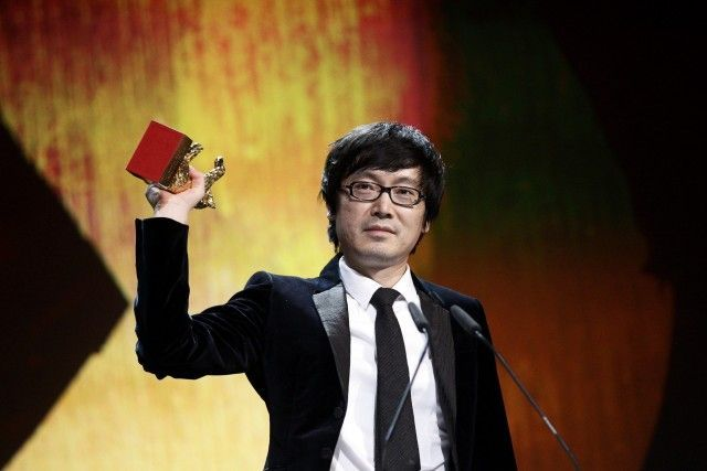 Chinese director Diao Yinan holds up the Golden Bear trophy during the awards ceremony of the 64th Berlinale International Film Festival in Berlin